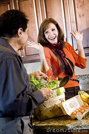 Mature couple having fun cooking in kitchen