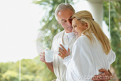 Mature couple holding coffee cups by copy space