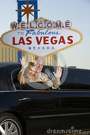 Mature Couple In Limousine Waving Hands