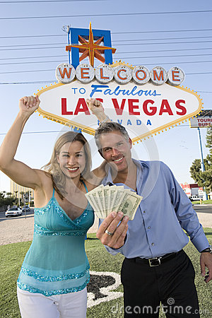 Mature Couple With Money And Welcome Sign In The Background