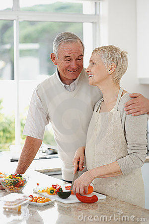 A mature couple preparing food in the kitchen