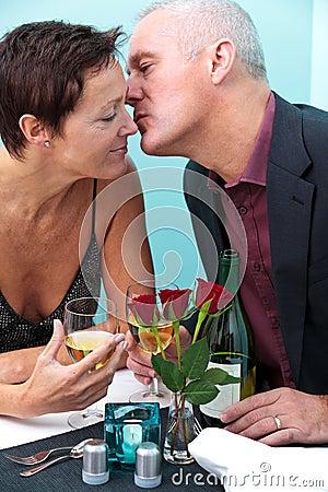Mature couple restaurant kiss