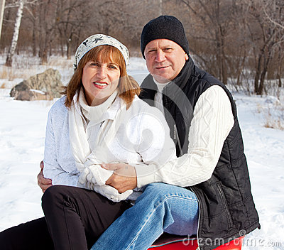 Mature couple sledding