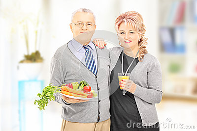 Mature couple standing close together holding a healthy food and