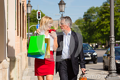 Mature couple strolling through city shopping