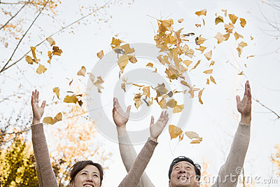 Mature Couple Throwing Leaves into the Air and Having Fun in in Autumn