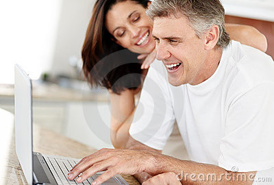 Mature couple using laptop computer and smiling