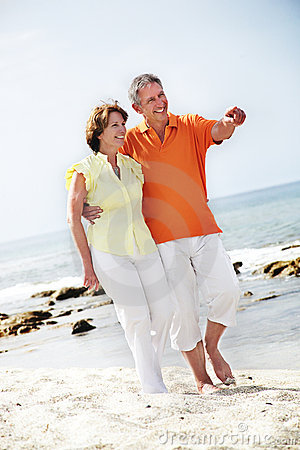 Free Mature Couple Walking Along The Beach. Royalty Free Stock Image - 12884926