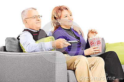 Mature couple watching TV and eating popcorn seated on a sofa