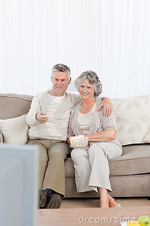 Mature couple watching tv in their living room