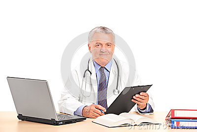 A mature doctor posing in his office