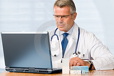 Mature doctor working on laptop