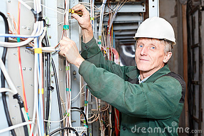 Mature electrician working in hard hat with cables