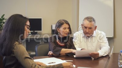 Mature family couple buying property and discussing mortgage contract with african-american saleswoman. Customers and lawyer sitting at desl in boardroom in stock video