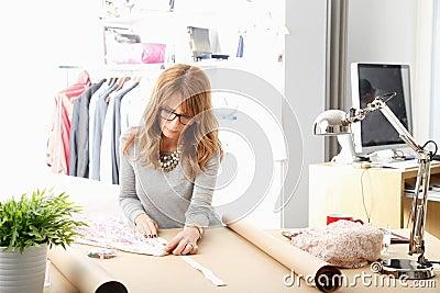 Mature fashion designer working in her studio
