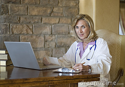 Mature female Doctor writing prescription