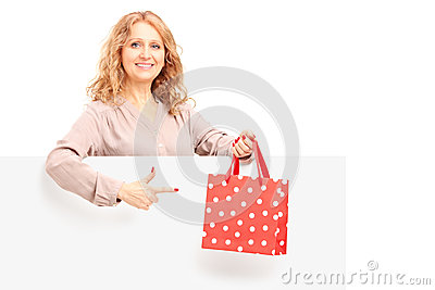 Mature female holding a bag and gesturing on a blank panel