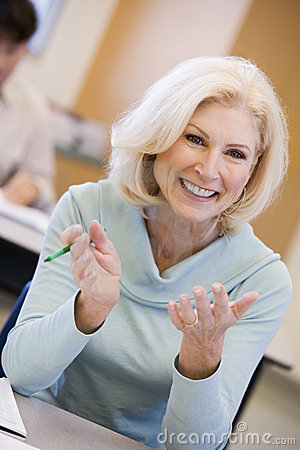 Mature female student gesturing in class