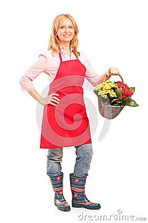 Mature florist holding a basket full of flowers
