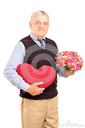A mature gentleman holding a red heart and flowers