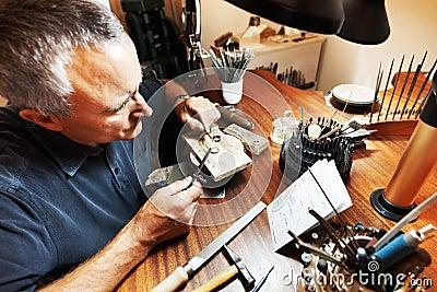 Mature goldsmith making a ring