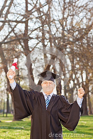 Mature graduate gesturing happiness in park
