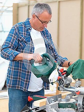 Mature handy man using an electric  saw