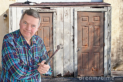 Mature handyman with hammer getting ready to tear