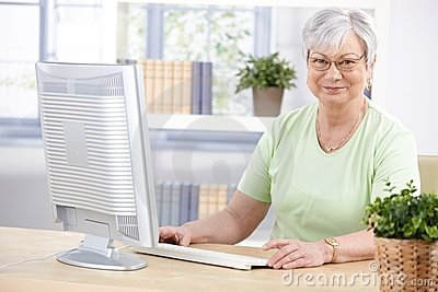 Mature lady with computer smiling