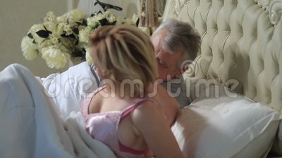 Mature loving couple lounging in bed after awaking stock video