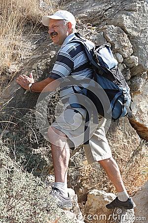 Mature man climbing on rock
