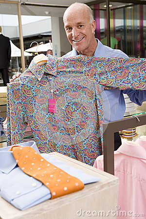 Mature man in clothing store, holding up shirt, smiling, portrait