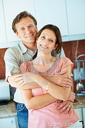 Mature man embracing a pretty woman in the kitchen