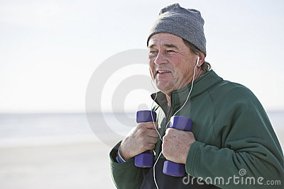 Mature man exercising with hand weights outdoors