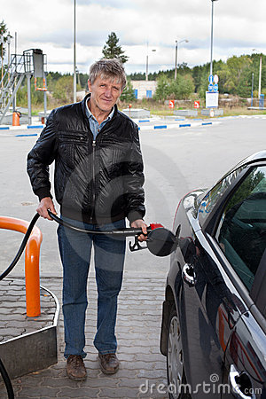Mature man filling car with gasoline in