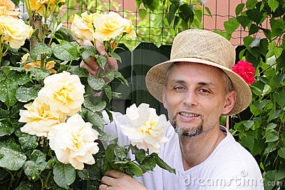 Mature man in garden between roses