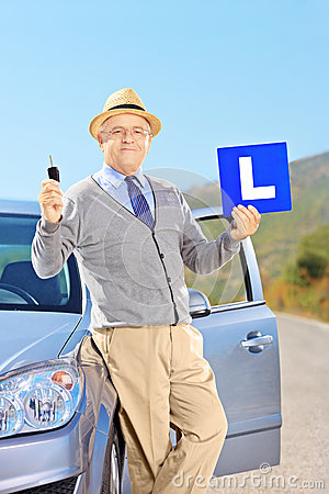 Mature man on his car holding a L sign and key after having his