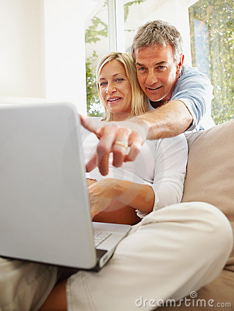 Mature man with his pregnant wife using a laptop