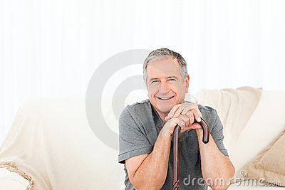 Mature man with his walking stick on his bed