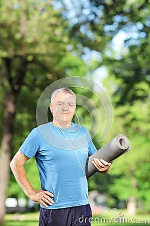 Mature man holding an exercising mat in park