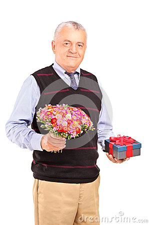 Mature man holding gift and bouquet of flowers