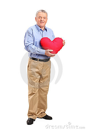 Mature man holding a red heart shaped pillow