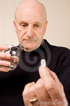 Mature  man holding tablet or pill with water