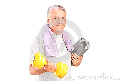 Mature man holding weight and mat