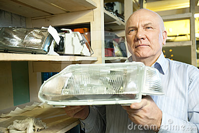 Mature man holds  automotive  headlight