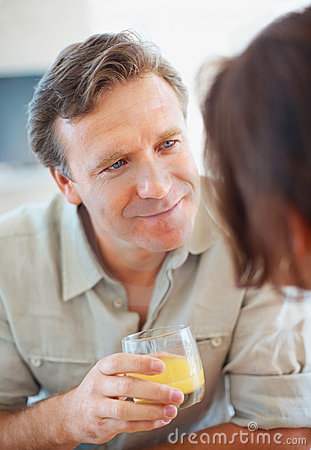 Mature man with a juice glass talking to a woman
