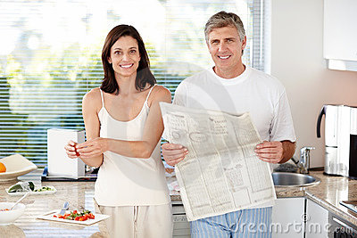 Mature man in kitchen and wife making breakfast