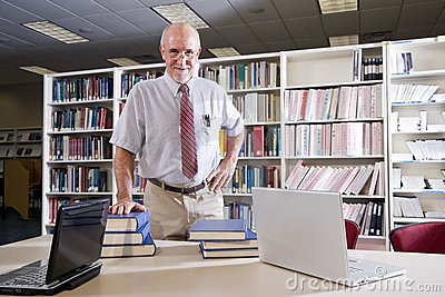 Mature Man At Library Table With Textbooks