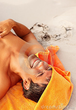 Mature man lying on the sand with the towel