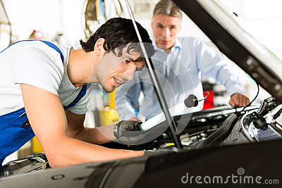 Mature man and mechanic looking at car engine